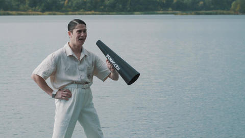 Man in hair net and white clothes standing on boat shouts into megaphone Footage