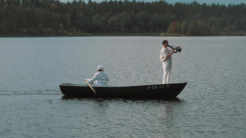 Nurse paddling boat on lake, man in white clothes commands into megaphone Footage