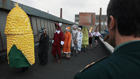 Bizarre scene, colonel command row of characters in costumes at industrial site Footage