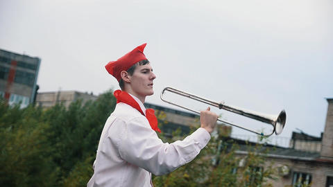 Soviet pioneer scout in red tie and hat blowing metal tube outside on windy day Footage