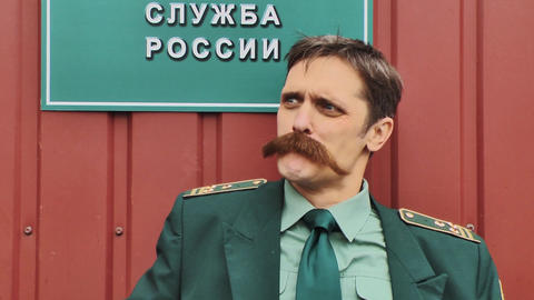 Russian army colonel with big mustaches talking in front of red wall Footage