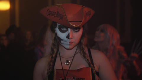 Woman in pirate hat and half painted face posing for camera at halloween party Live Action
