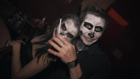 Couple with skeleton skull face paint and posing for camera at night club Footage