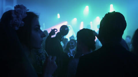 Crowd of young people in halloween costumes spending time at night club party Live Action