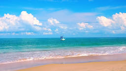 Beautiful seascape with sandy beach washed by azure sea and small fishing boat Footage