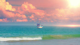 Fishing boat floating on waves of sea washing tropical sandy coast at sunset Footage