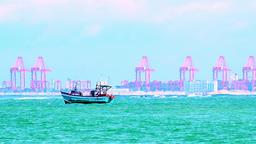 Fishing boat swaying on waves of azure sea against marine port cargo terminal Footage