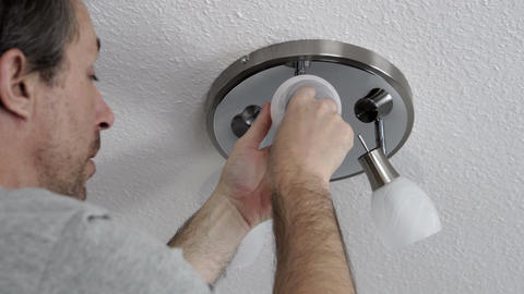 Man Changing Lightbulb on Ceiling Fixture Closeup Footage