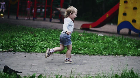 Blonde little boy running on playground in summer park. Childhood. Flying doves Footage
