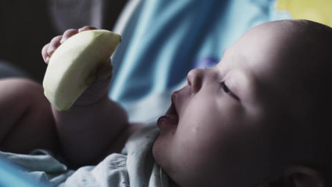 Adorable cute baby sitting at children table eating pear. Mother. Feeding. Child Footage