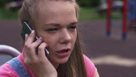 Young attractive girl with freckles speak to phone on playground. Summer park Footage