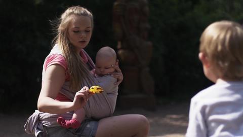 Young mother hold baby in sling, playing with son on playground. Summer day Footage