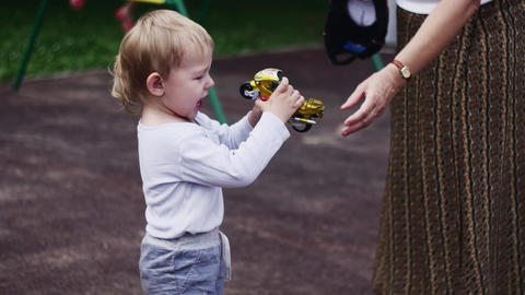 Woman give back motorbike toy to crying boy on playground. Sunny day. Childhood Live Action