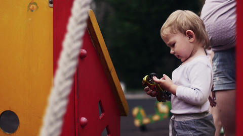 Little boy on playground play with motorbike toy. Sunny day. Childhood. Family Footage