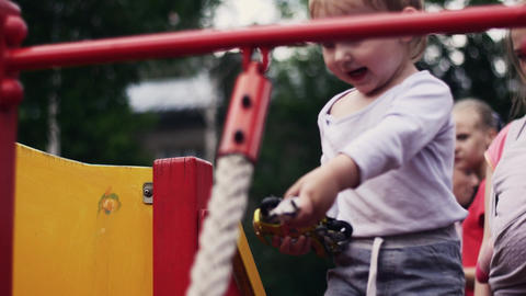 Little boy on playground play with toy. Mother with baby. Childhood. Family Live Action