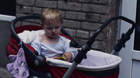 Little boy play with toy in baby carriage on street. Summer walking. Child Footage