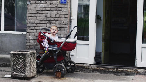 Little boy play with toy in baby carriage on street at shop. Summer walking Footage