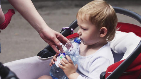 Little blonde boy drink water from bottle in baby carriage on street. Summer day Footage