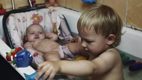 Little boy play with fish toys in bathtub. Baby swim in cradle. Happiness. Kids Footage