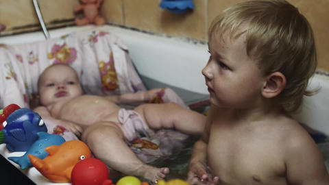 Little boy play with toys in bathtub. Baby swim in cradle. Young mother. Kids Footage