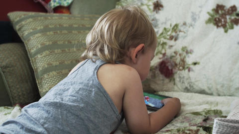 Back side of little boy on sofa watching video on smartphone. Childhood. Device Footage