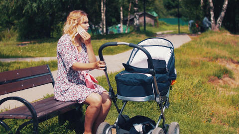 Mother with baby carriage and speaking on phone in summer park. Sunny. Walking Footage