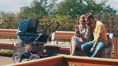 Young parents with baby carriage on bench. Using smartphone. Family. Playground Footage