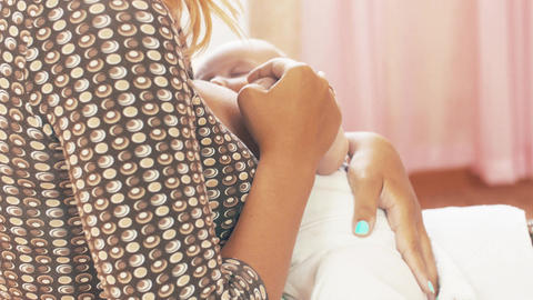 Young mother breastfeeding little baby. Motherhood. Holding hand. Family Footage