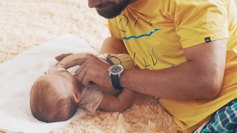 Bearded father lie with baby. Hold baby dummy. Parent. Family. Communication Footage