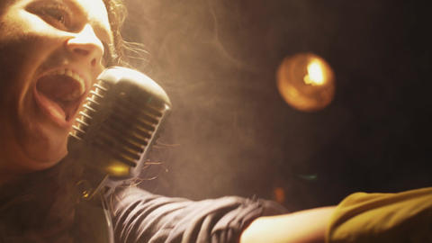Scrubwoman sing in vintage microphone on stage of club. Dance under spotlight Footage