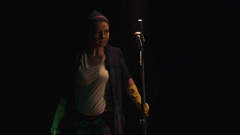 Scrubwoman with mop and bucket slowly come on stage to vintage microphone Footage
