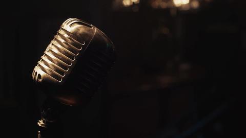Vintage microphone on stage under spotlight. Scrubwoman lie on bar stand Footage