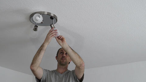 Man Changing Ceiling Fixture Light Bulb Footage