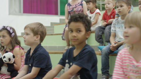 Afro American Boy Sits on Stairs between Caucasian Children Footage