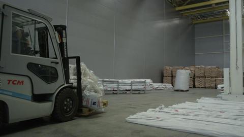 Loader Transports Polyethylene Pipes along Large Warehouse Live Action