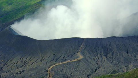 People walk on lava rock to active Bromo volcano crater. Indonesia Footage