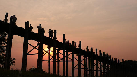 U Bein bridge people silhouettes at sunset smooth dolly shot w sound Footage