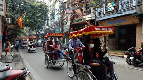 Tourists ride a rickshaw in Hanoi Footage
