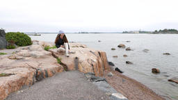 Woman sit alone at large stone on shore, look to distance, autumn season Footage