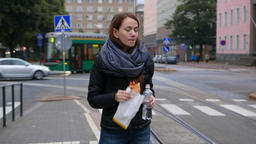 Young woman has a quick bite, stand on city street at evening time Footage