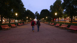 Young adult couple walks away at empty evening alley in... Stock Video Footage