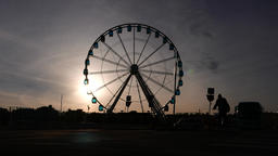 Bicycle and two cars ride against Ferris Wheel silhouette, high contrast shot Footage