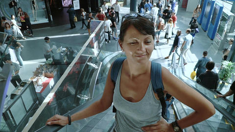 Smiling woman moving up on an escalator Filmmaterial