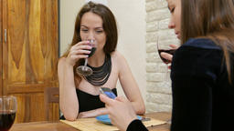 Girls drink wine, have small talk, one look to smartphone, portrait shot Footage