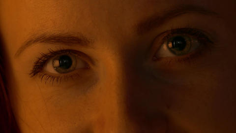 4K Young Woman Eyes Close-Up Under Warm Low-Key Lighting Footage