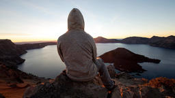 Parallax 2.5D Hooded guy sitting on a rock watching sunrise above crater lake
