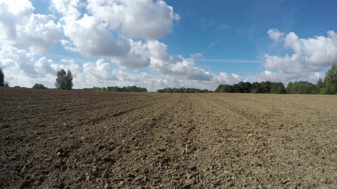 freshly plowed agriculture field and autumn clouds, time lapse 4K Footage