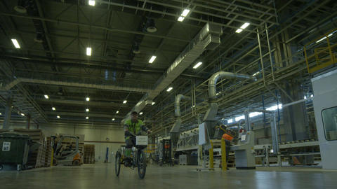 Worker Rides Three-wheels Bike along Plant Workshop Footage