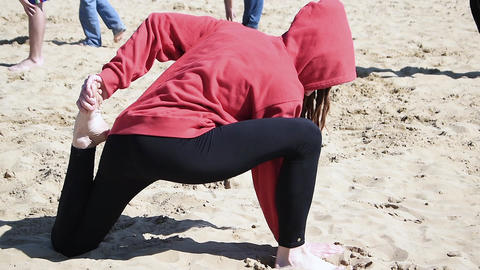 Active young woman streching on the sand