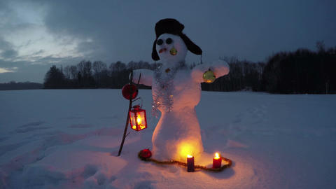 Snowman on new year snowy field and candle lights, time lapse 4K Footage